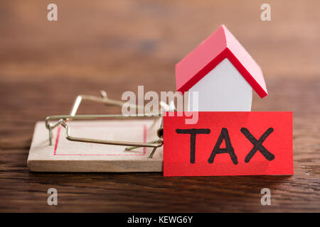 Tax Concept With House Model On Mousetrap At Wooden Desk - Stock Photo