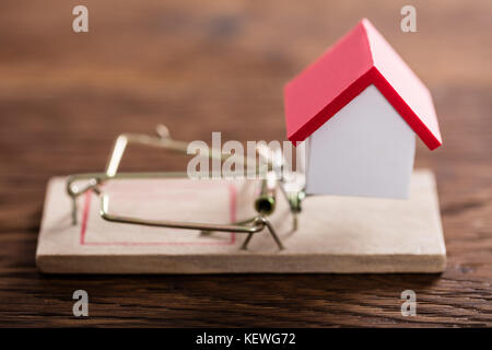 Close-up Of A House Model On Mousetrap At Wooden Desk - Stock Photo