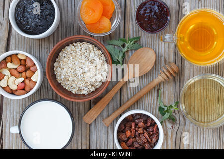 Oat flakes, dried fruits and yogurt, nuts and honey. Concept: proper nutrition. Healthy food - Stock Photo