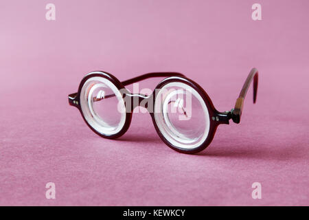 Old fashion design spectacles eyeglasses on pink violet paper background. Vintage style men fashion accessories - Stock Photo