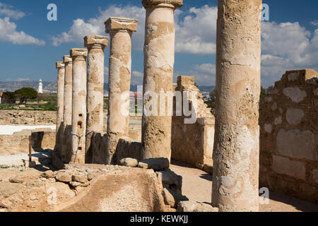 Columns in the UNESCO world heritage Kato Paphos Archaeological Park with Paphos harbour lighthouse in the background, - Stock Photo