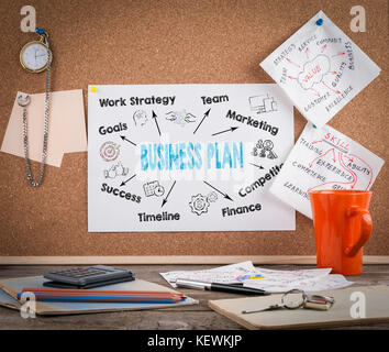 business plan concept on cork board. Wooden office desk with a big mess - Stock Photo
