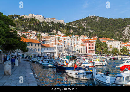 Looking up the gently sloping tree-shaded hillside towards the medieval castle seen from the harbour in Hvar Town. - Stock Photo