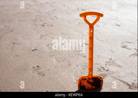 Toy spade stuck in the sand on a beach - Stock Photo
