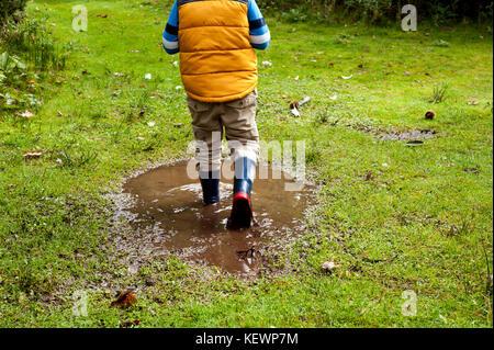 Boy having fun splashing in muddy puddles - Stock Photo