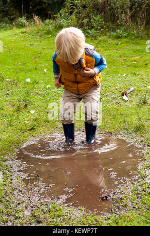Boy having fun splashing in muddy puddles - Stock Photo