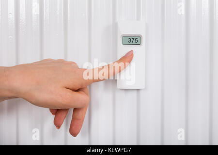 Close-up Of Person's Hand Adjusting Temperature With Digital Thermostat - Stock Photo