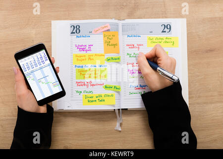 High Angle View Of A Businesswoman Writing Schedule In Diary Using Mobilephone On Wooden Desk - Stock Photo