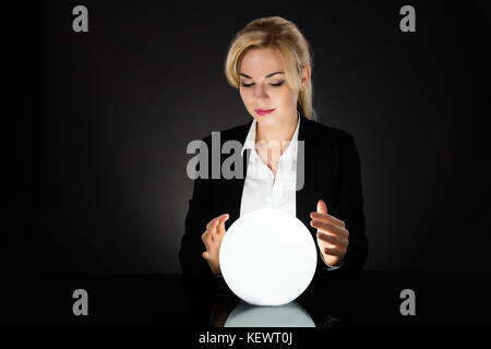 Businesswoman Looking Into The Future In A Crystal Ball On Black Background. Fortune Teller Predicting Future - Stock Photo