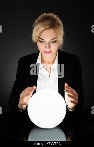 Young Businesswoman Looking Into The Future In A Crystal Ball On Black Background. Fortune Teller Predicting Future - Stock Photo
