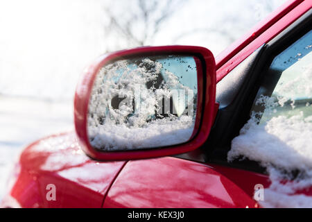 Snow covered red car parked outside, with focus on rear view mirror, winter transport issues - Stock Photo