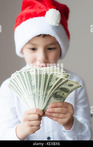 happy cute boy in Santa hat holding hundred-dollar bills pack - Stock Photo
