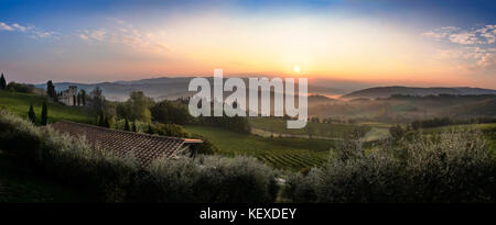 Beautiful sunrise over Castellina in Chianti with some fog between the hills with vineyards in Tuscany in Italy - Stock Photo
