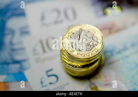 British currency - pile of new (2016) pound coins on £5 £10 and £20 notes - Stock Photo