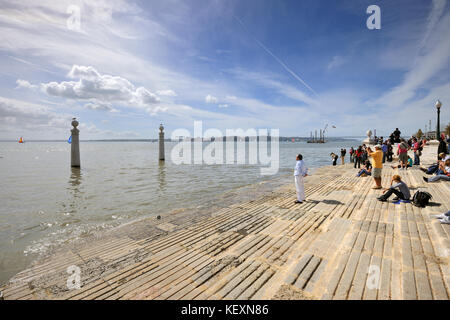 Solitary man in front of the Tagus river. Cais das Colunas, Lisbon, Portugal - Stock Photo