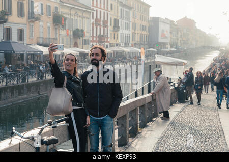 A couple take a selfie picture at Milan, Italy's Navigli Grande canal during a misty afternoon. Navigli is a bohemian - Stock Photo
