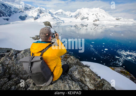 A passenger from an Antarctic cruise ship amongst stunning coastal scenery beneath Mount Walker in Paradise Bay - Stock Photo