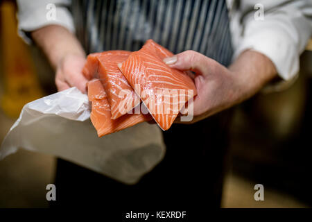 Close up of a fish monger's hands holding three fillets of fresh filleted salmon on a market stall in Yorkshire, - Stock Photo