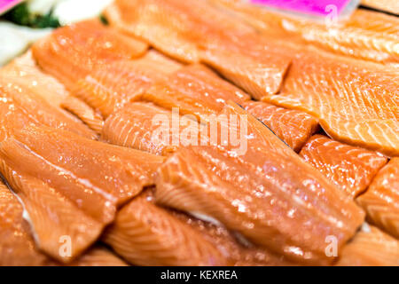 Close up of salmon fillets spread over ice on a fish monger's market stall in Yorkshire, England, UK - Stock Photo
