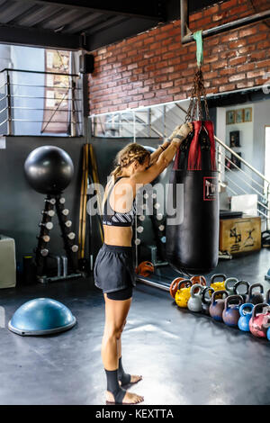 Photograph with side view of young woman hanging punching bag in kickboxing gym, Seminyak, Bali, Indonesia - Stock Photo