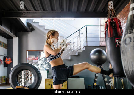 Side view photograph of female kickboxer kicking punching bag, Seminyak, Bali, Indonesia - Stock Photo