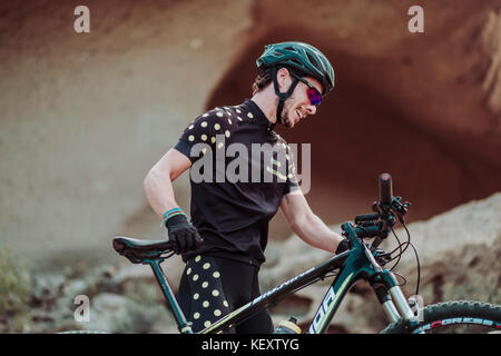 Man walking in desert with his mountain bike, Tenerife, Canary Islands, Spain - Stock Photo