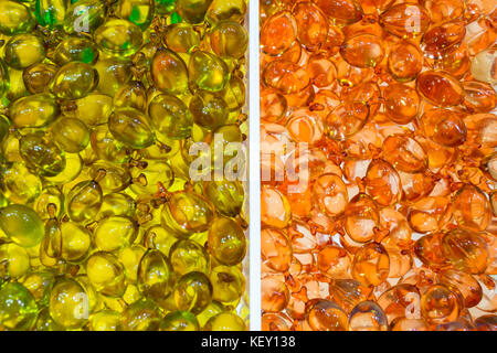 hair and skin vitamin serum in orange and green soft capsules, background and texture - Stock Photo