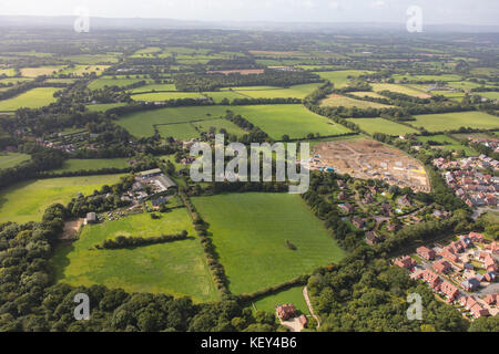An aerial view illustrating housing development around the edge of a Sussex town - Stock Photo