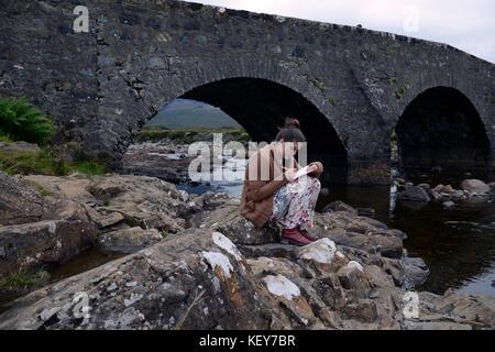 17 year old girl writes in her journal at old stone bridge over River Slichagan  Isle of Skye, Scot - Stock Photo