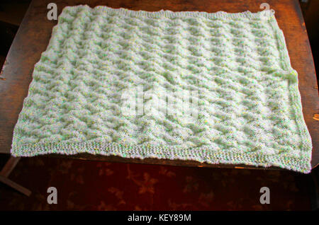 A lovely soft hand knitted baby blanket in colours of pastel shades white, yellow and green. Which has a chevron - Stock Photo