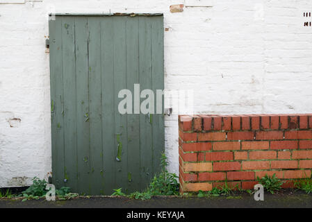 Old faded green wooden door with flaky paint in white brick wall - Stock Photo