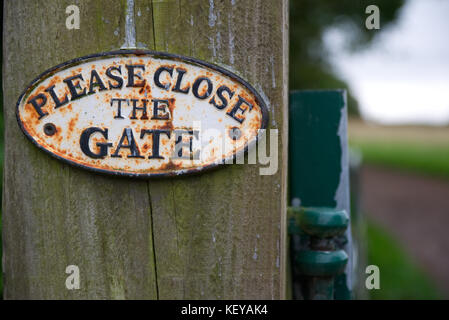 Weathered old Please Close The Gate sign on wooden post with path in the background