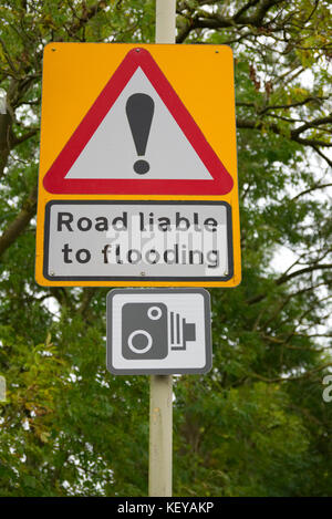 Road liable to flooding traffic warning sign with speed camera sign with greenery in the background - Stock Photo