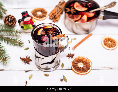 mulled wine in a glass with an iron cup holder on a white wooden background - Stock Photo