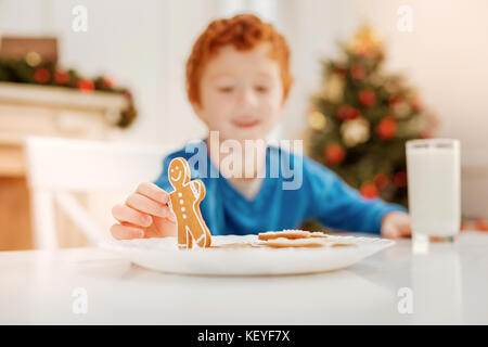 Joyful ginger boy playing with gingerbread man at table - Stock Photo