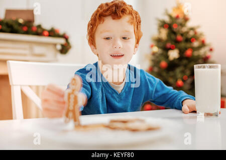 Happy curly haired kid playing with gingerbread man - Stock Photo