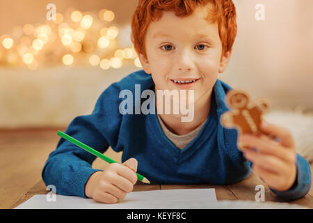 Adorable redhead child drawing on floor - Stock Photo