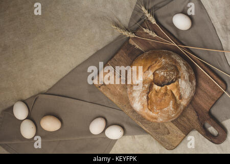 Homemade white wheat bread served with eggs and ears of wheat - Stock Photo