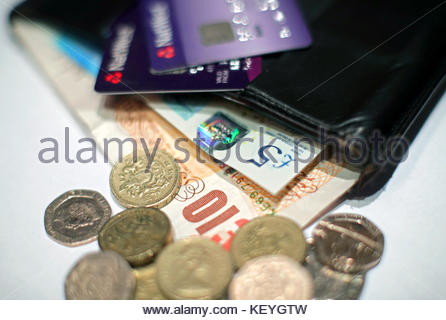File photo dated 29/1/2017 of coins and a five pound and ten pound banknotes and cards in a wallet. People struggling - Stock Photo