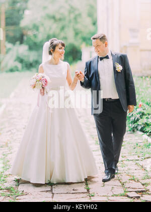 Happy charming newlywed couple is walking along the street. - Stock Photo