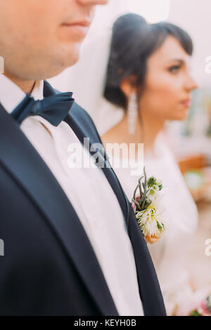 The side view of the boutonniere of the exotic flowers on the facket of the groom. - Stock Photo