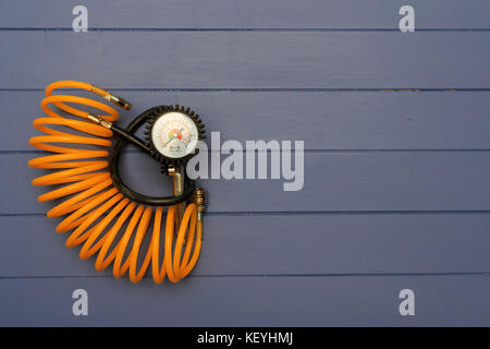 Tyre Inflater with air pressure gauge and yellow curled hose on blue wooden boards - Stock Photo