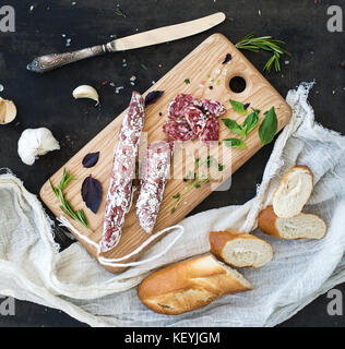 Meat gourmet snack. Salami, garlic, baguette and herbs on rustic wooden board - Stock Photo