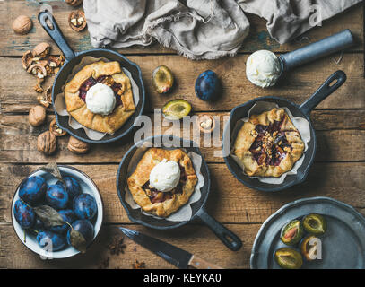Plum and walnut crostata pie with ice-cream scoops - Stock Photo