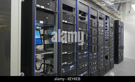 Many powerful servers running in the data center server room. Many servers in a data center. Many racks with servers - Stock Photo
