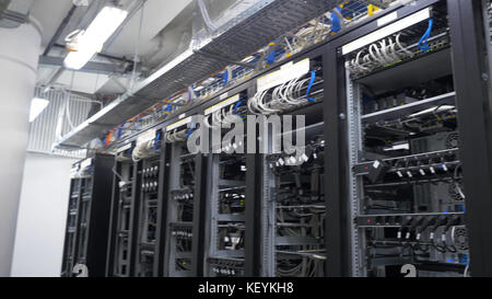 Row of bitcoin miners set up on the wired shelfs. Computer for Bitcoin mining. cables plug to motherboard for mining - Stock Photo