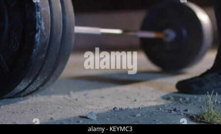 barbell for deadlift and foot athlete powerlifter competitions in powerlifting. Young athlete getting ready for - Stock Photo