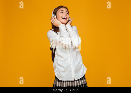 Portrait of a happy teenage schoolgirl in uniform with headphones singing while listening to music isolated over - Stock Photo