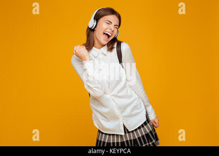 Portrait of a cheerful teenage schoolgirl in uniform with headphones enjoys listening to music isolated over orange - Stock Photo