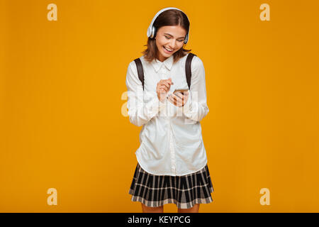 Portrait of a laughing teenage schoolgirl in uniform with headphones using mobile phone isolated over orange background - Stock Photo